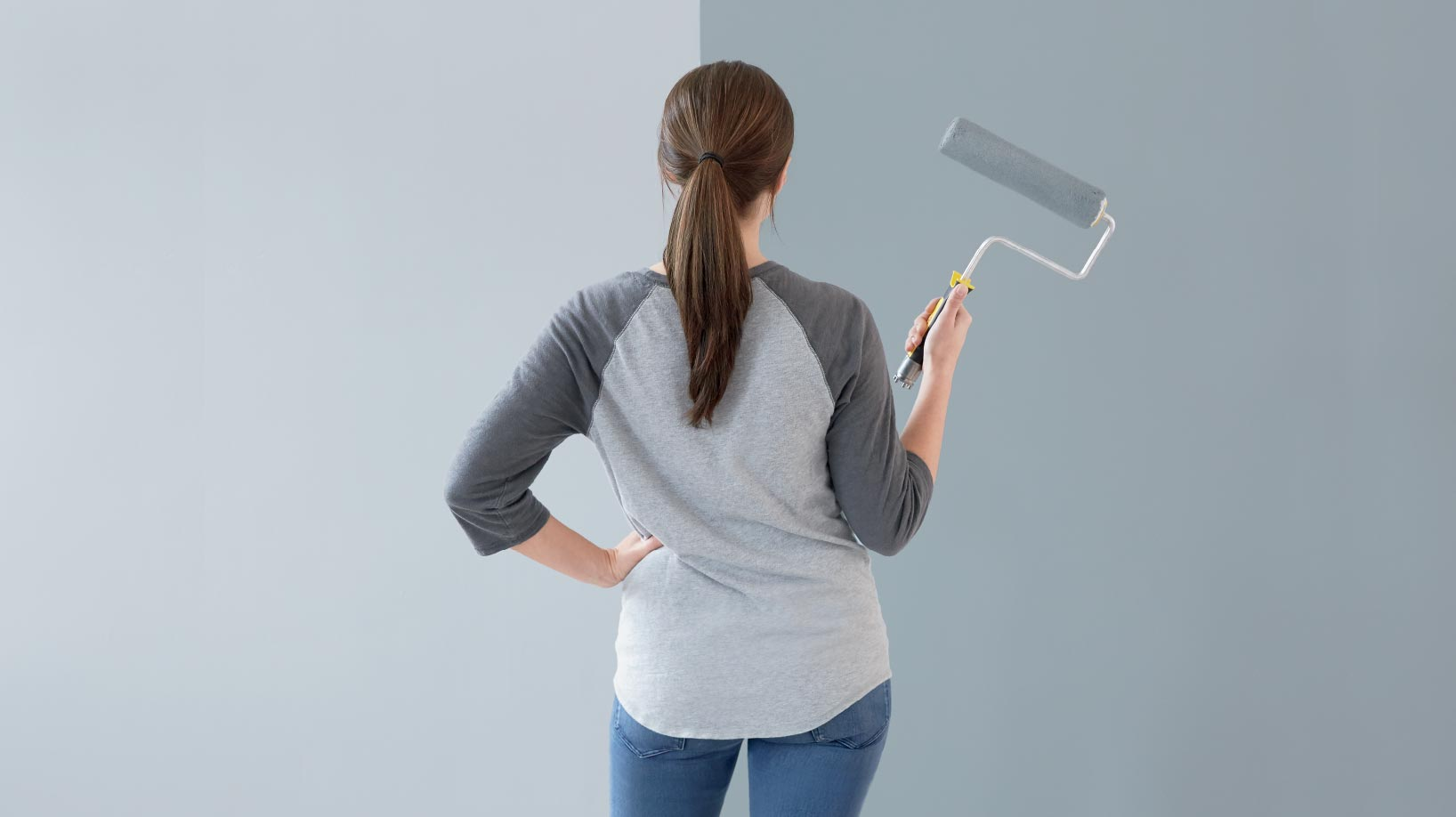 Woman with roller facing wall and contemplating wall colors