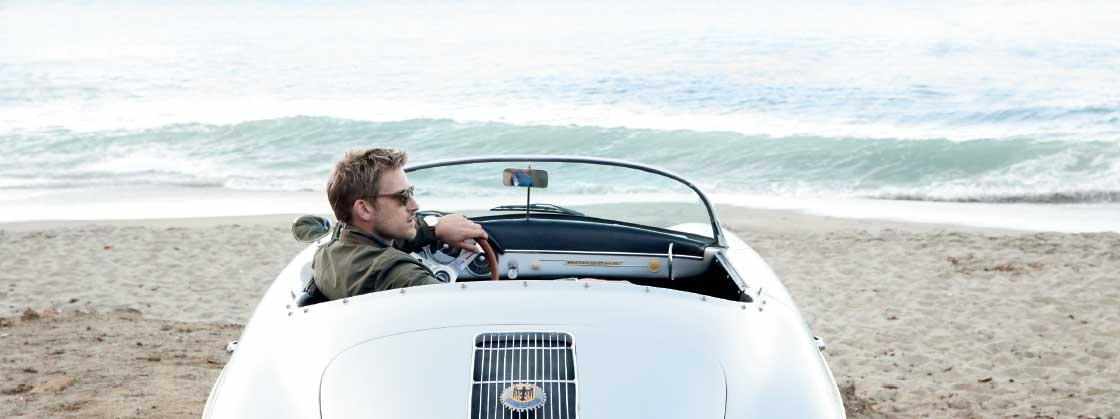 Car on beach with man wearing Peter Millar clothing