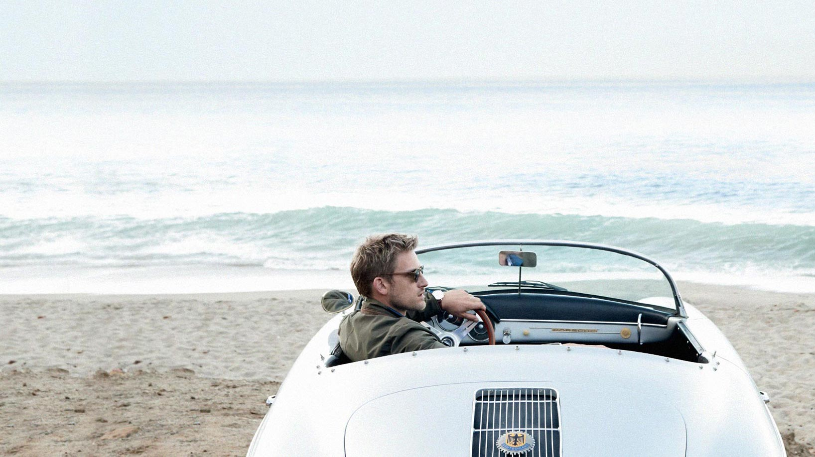 Man in Convertible Car on Beach Wearing Peter Millar Clothing