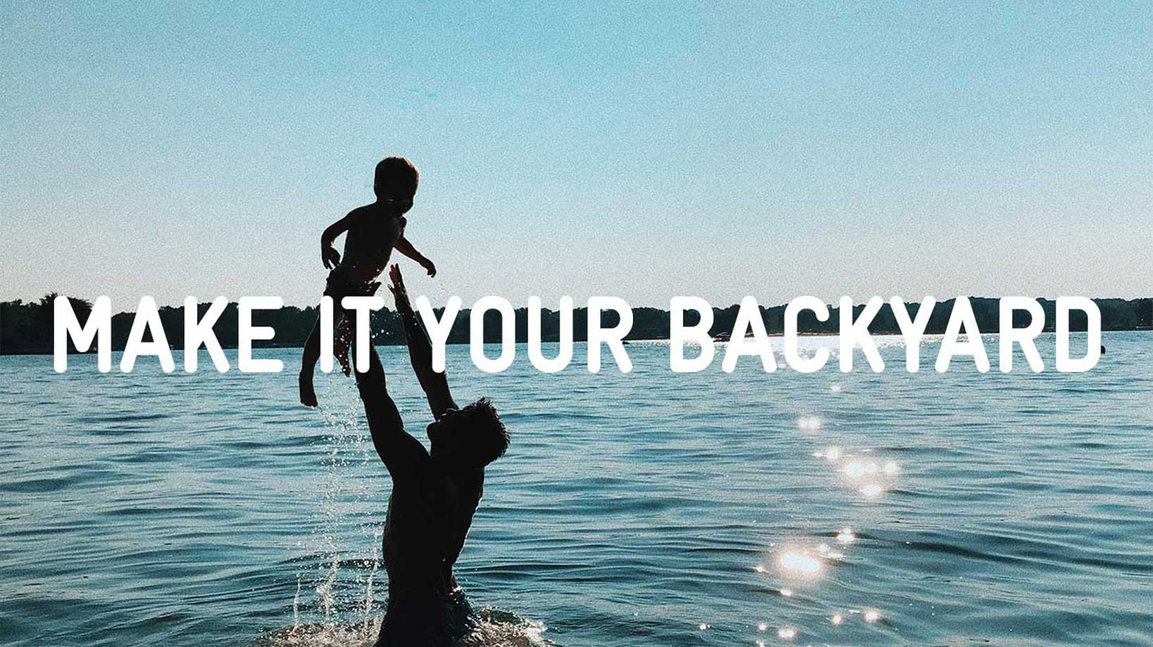 make it your backyard father holding child in lake