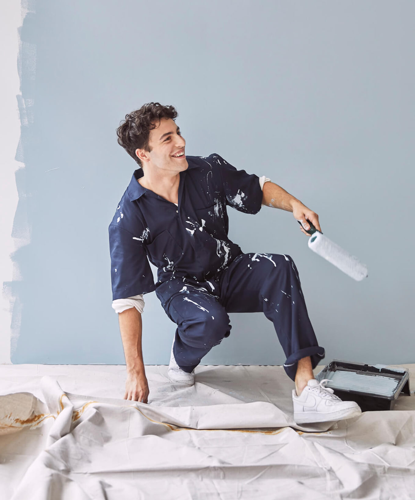 Paint stained man with roller smiling and painting wall