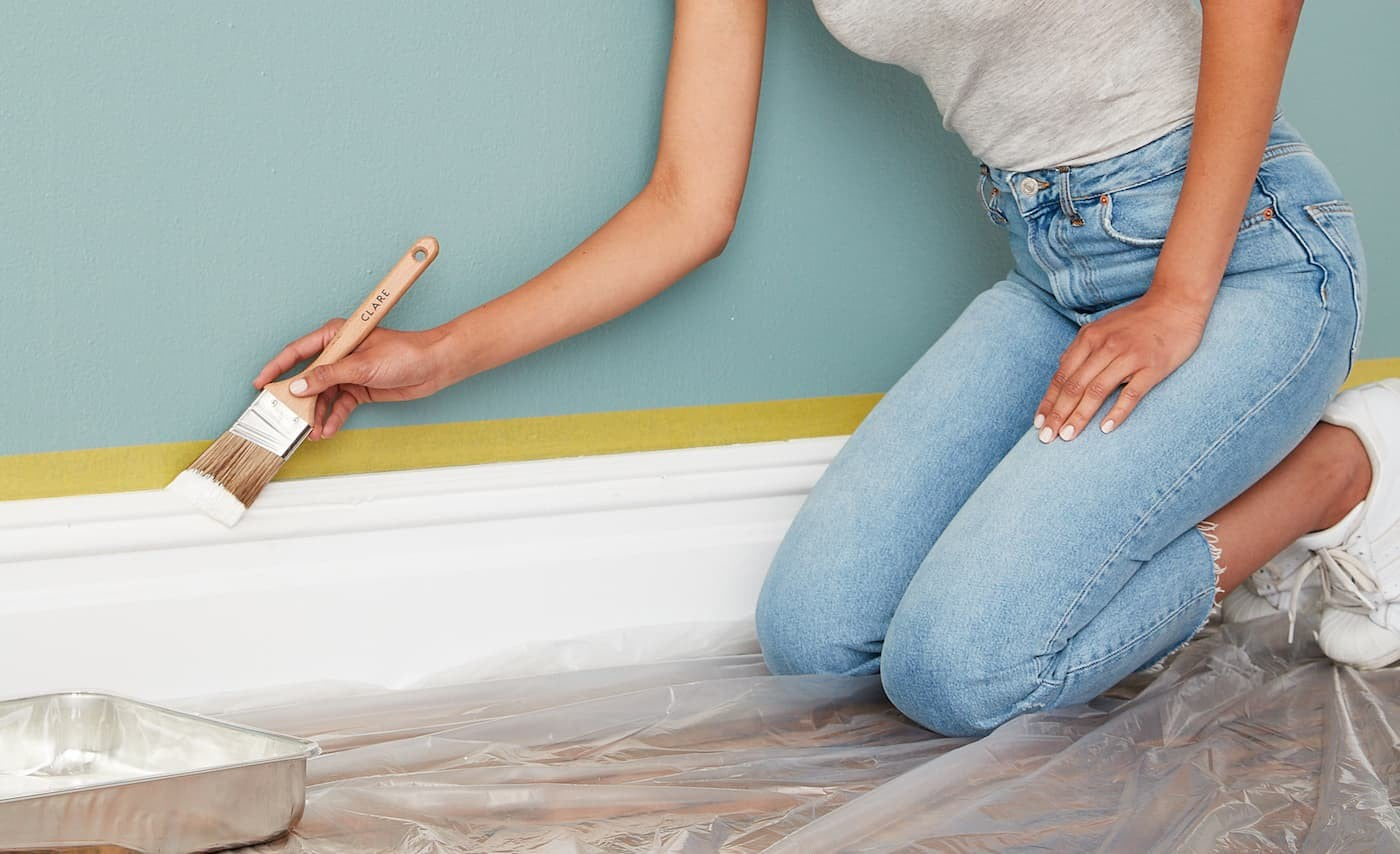 Woman painting floor trim with colorful walls in the background