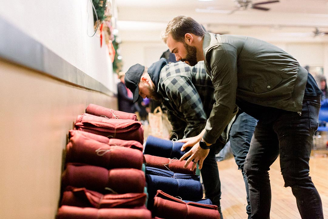 Man arranging blankets in piles ready to be distributed to the homeless