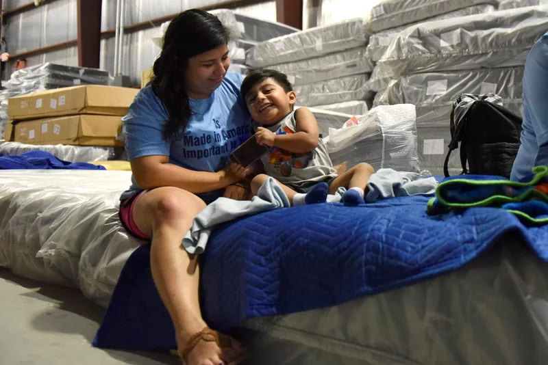 Mom and son smiling and sitting on mattresses in a warehouse