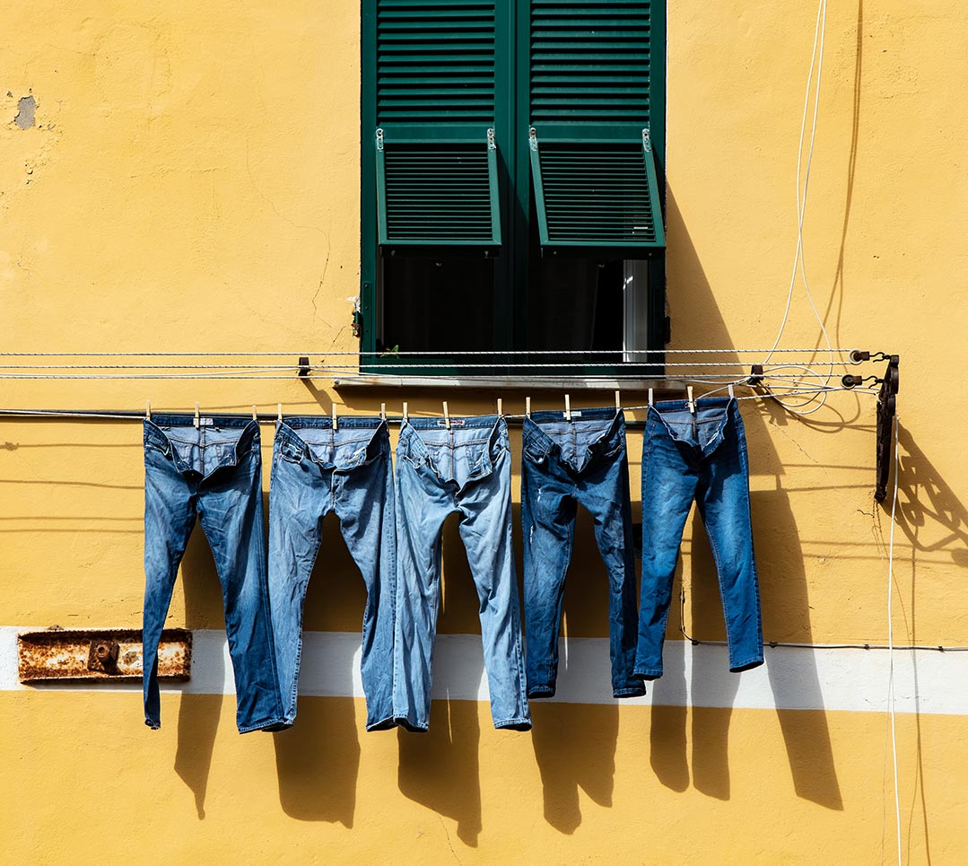 Jeans Hanging On a Clothesline Outside a Colorful Building