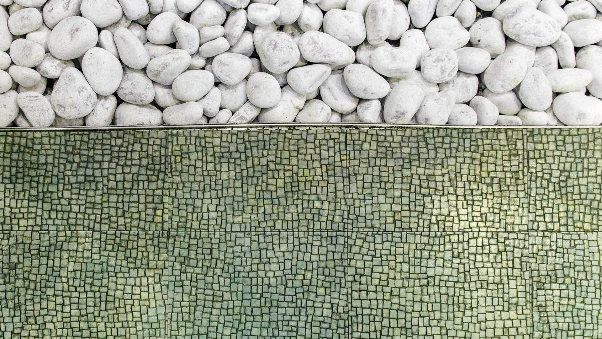 Textural image showing two different textures: round gray rocks and a mosaic wall