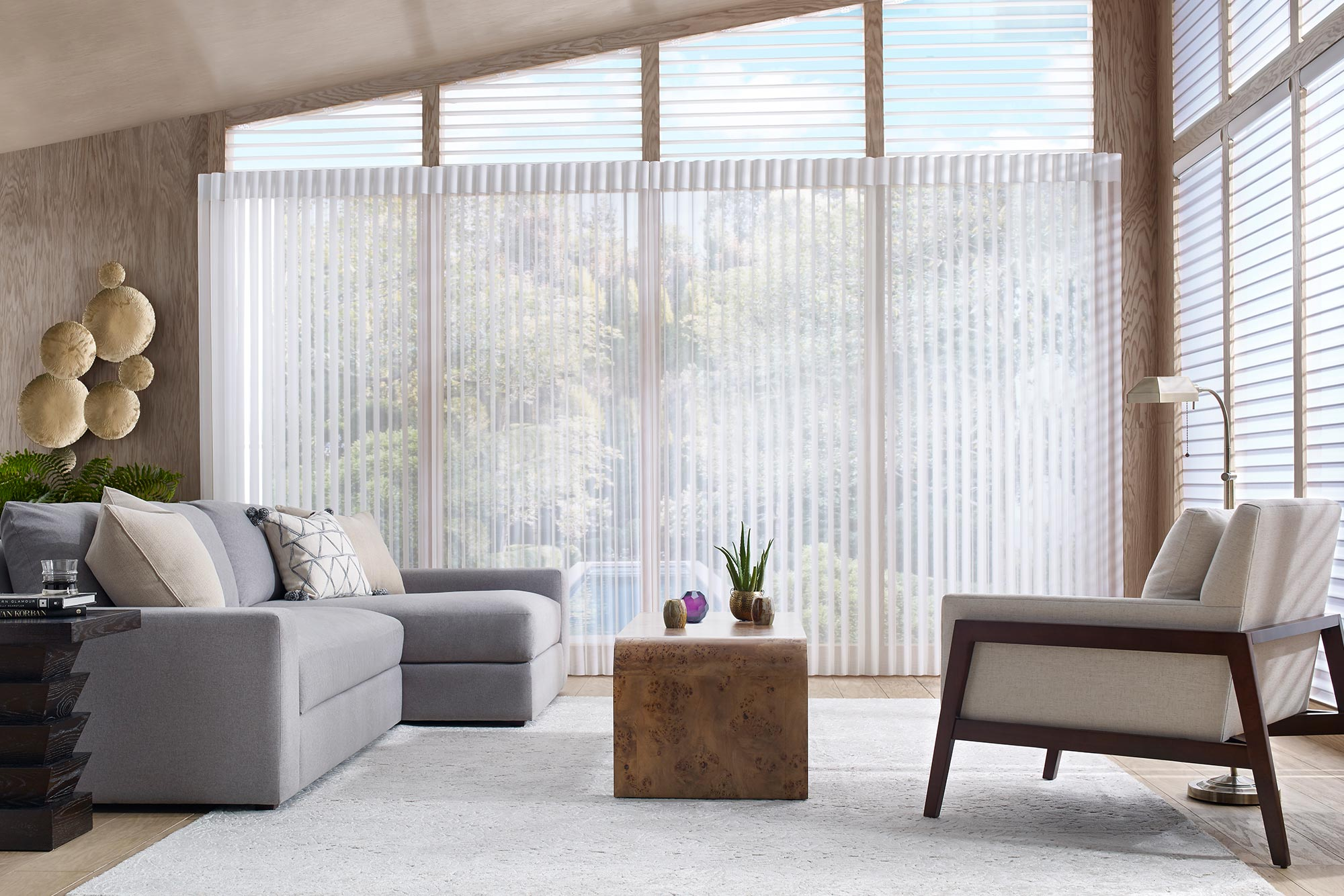 Room scene showing sofa and chairs in front of a window with luxurious blinds