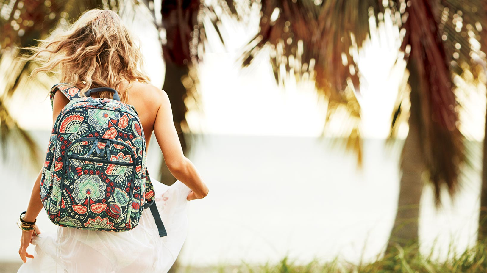 Girl walking on beach with patterned backpack from Vera Bradley