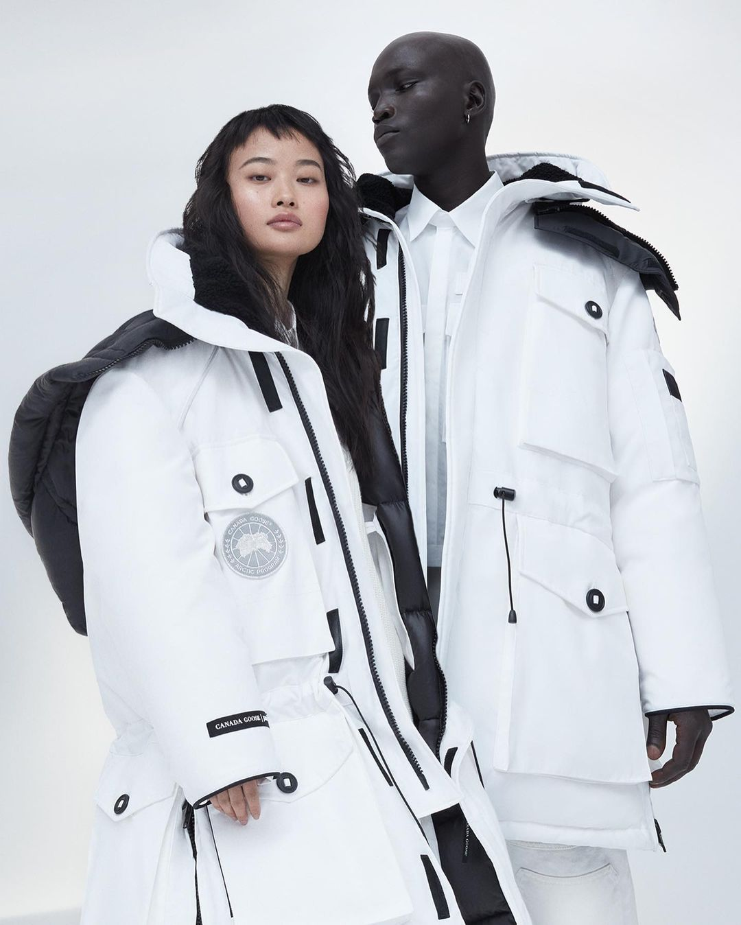 two people wearing white winter jackets