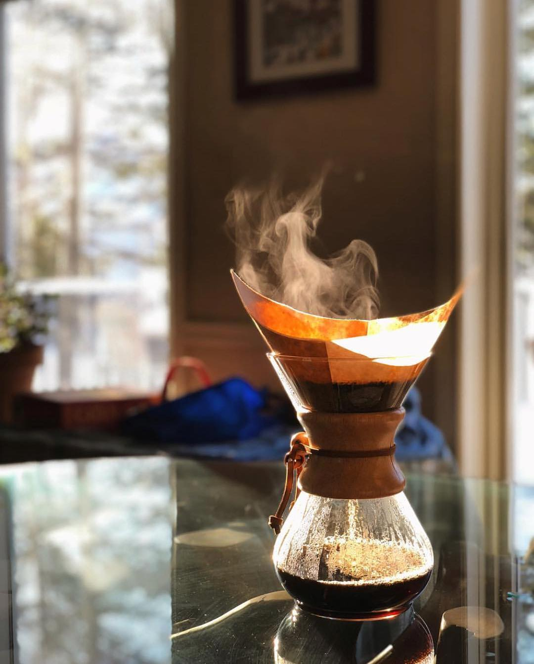 pour over container with coffee in it and steam on the kitchen counter