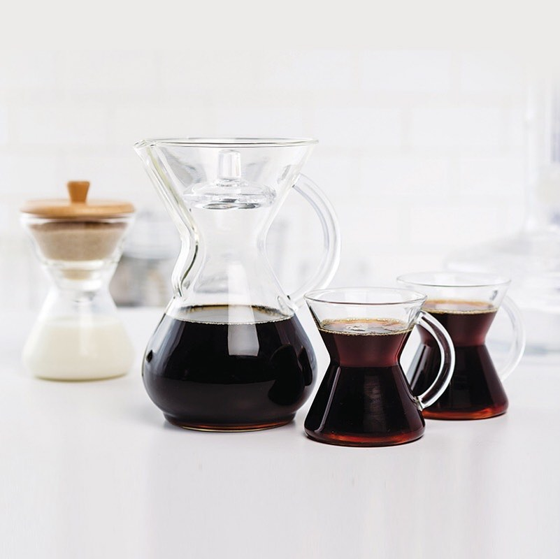 pour over coffee container with two glass cups of coffee and milk in a container