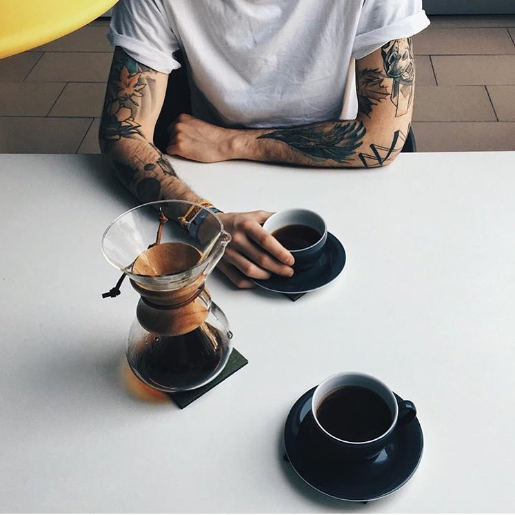 person with tattoos on arms in white shirt sits at table drinking coffee