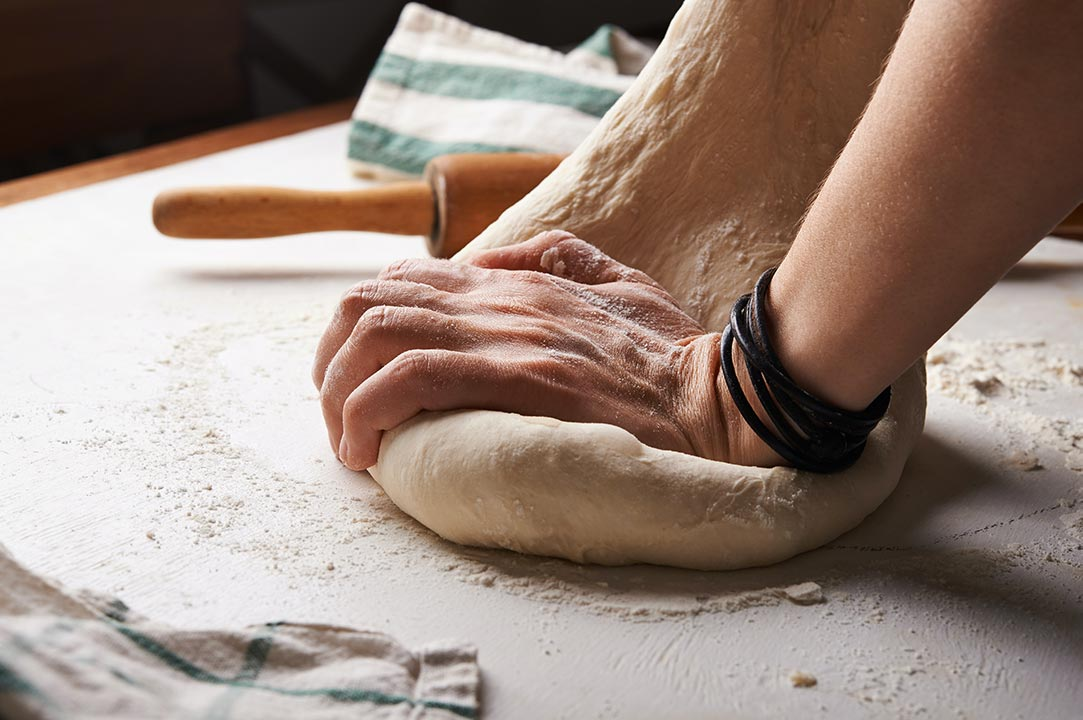 person rolling out dough on the counter