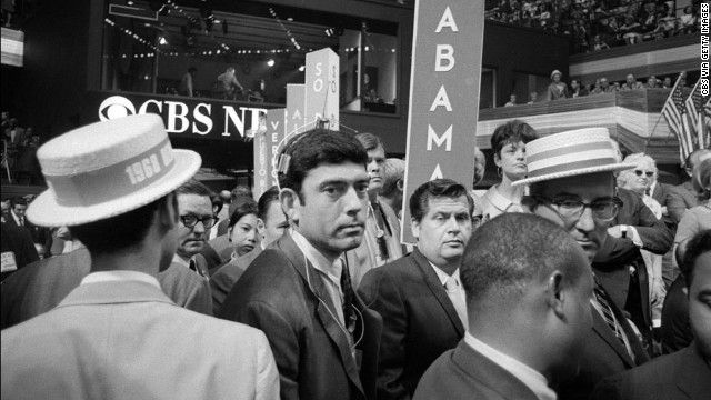 black and white photo guy looking at camera in a crowd