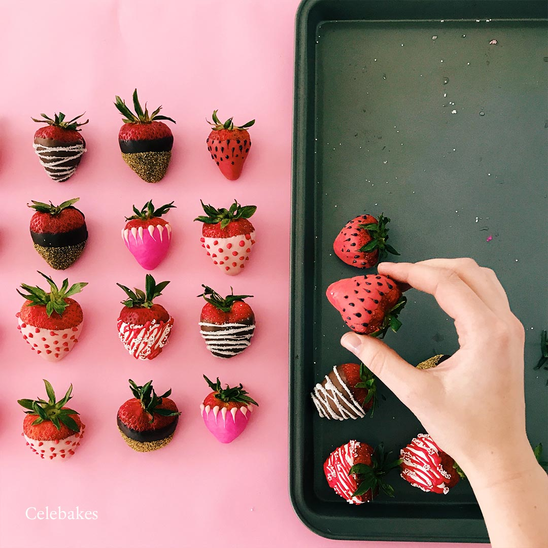 strawberries dipped in chocolate with hand placing one on cookie sheet