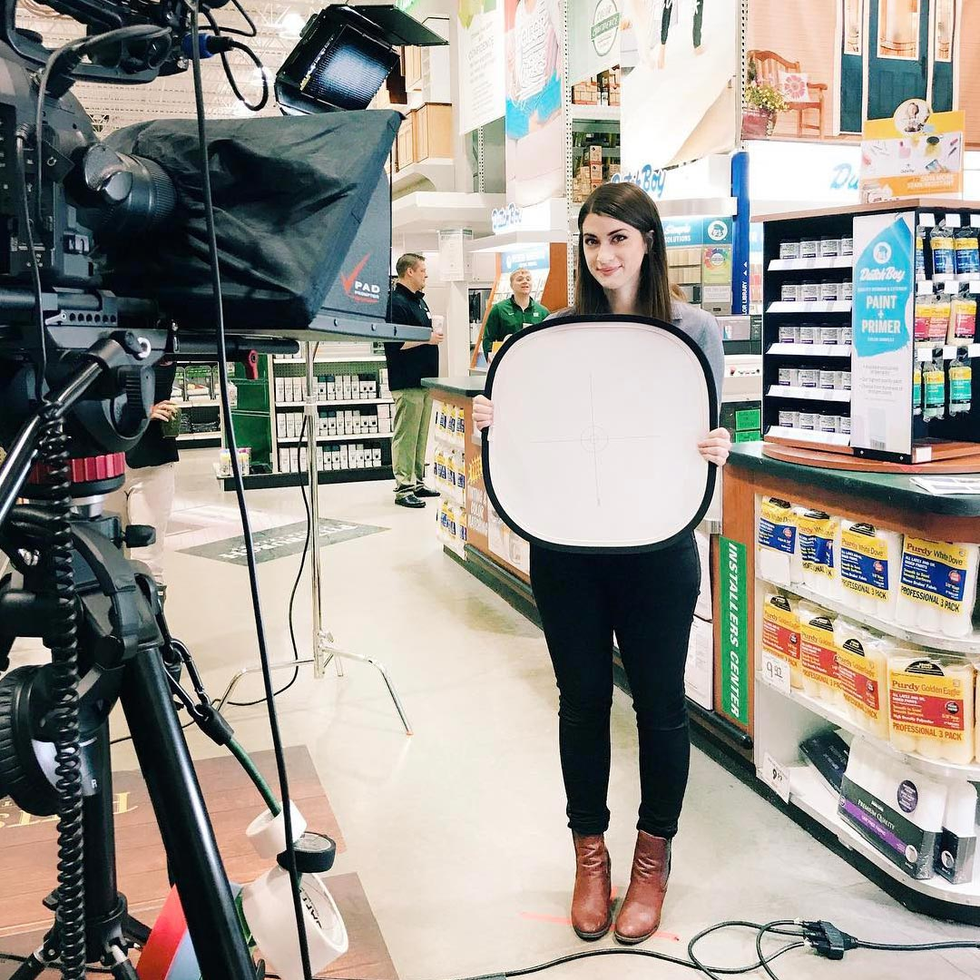 woman standing with white screen in front of camera in aisle