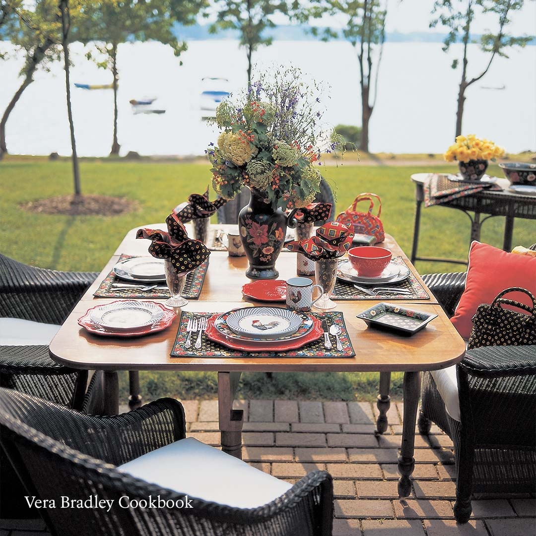 outdoor dining set with plates in front of a lake