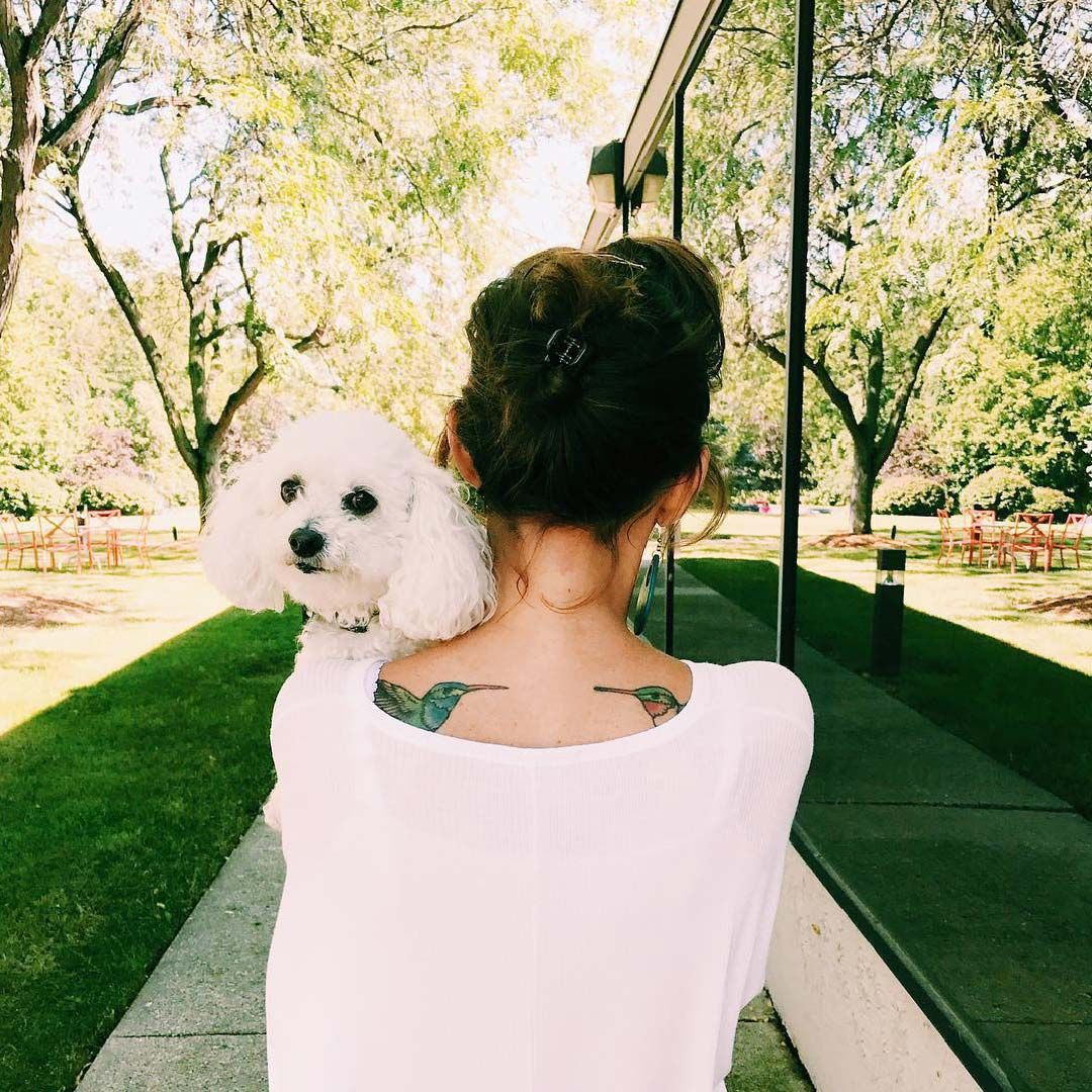 woman outside holding dog looking back