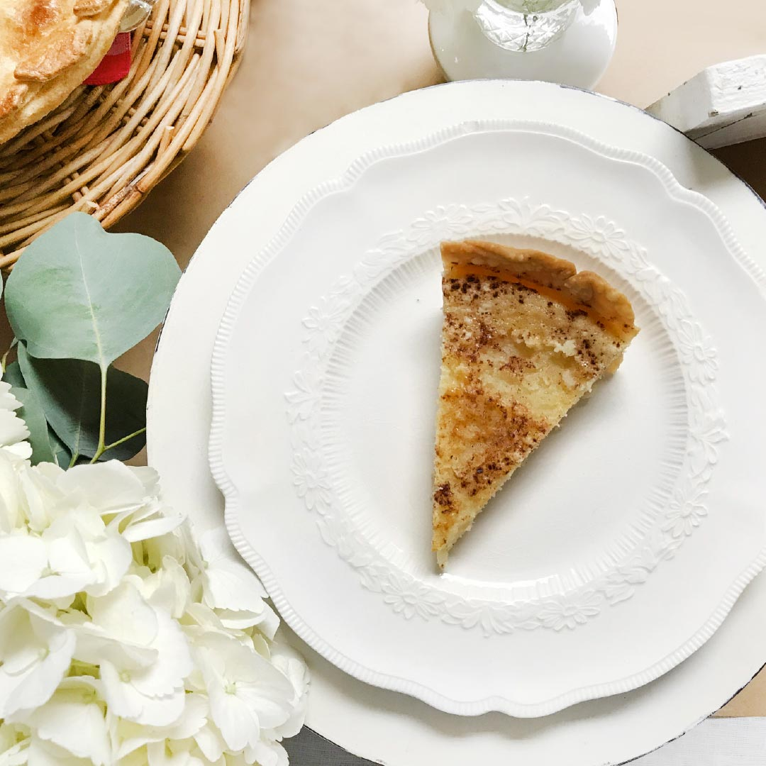 layered plates with a piece of pie and flowers