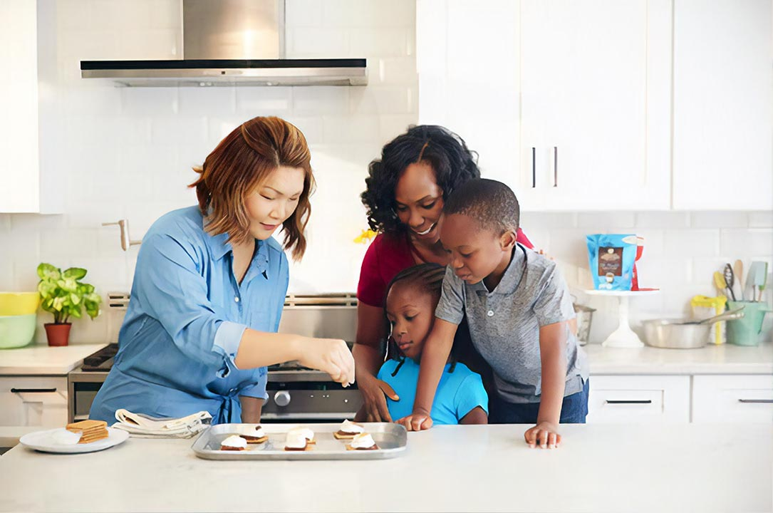 two women in kitchen with two kids cooking